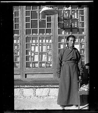 Gyalo Thondup - Gyalo Thondup in 1948 or 1949, standing in front of a large window of the Dalai Lama's family house, Yabshi Taktser, in Lhasa. He is wearing a woollen robe and felt boots. The bottom part of a bird cage can be seen at the top of the image.