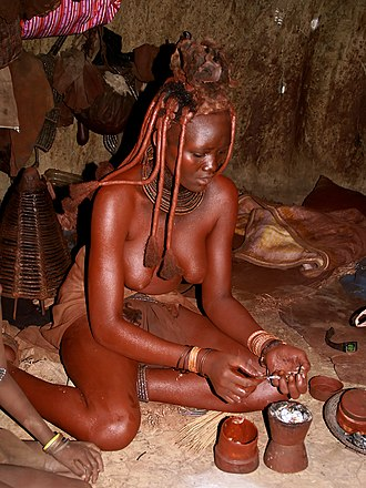 Himba people - Himba woman preparing incense, the smoke is used as a antimicrobial body cleansing agent, deodorant and fragrant, made by burning aromatic herbs and resins.