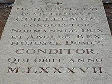 """Dans la pierre est inscrit: """"Hic sepultus est invictissimus Guillelmus Conquestor, Normanniæ Dux, et Angliæ Rex, hujus ce Domus, Conditor, qui obiit anno M.LXXXVII."""""""