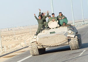 Iraqi military men riding on tank.jpg