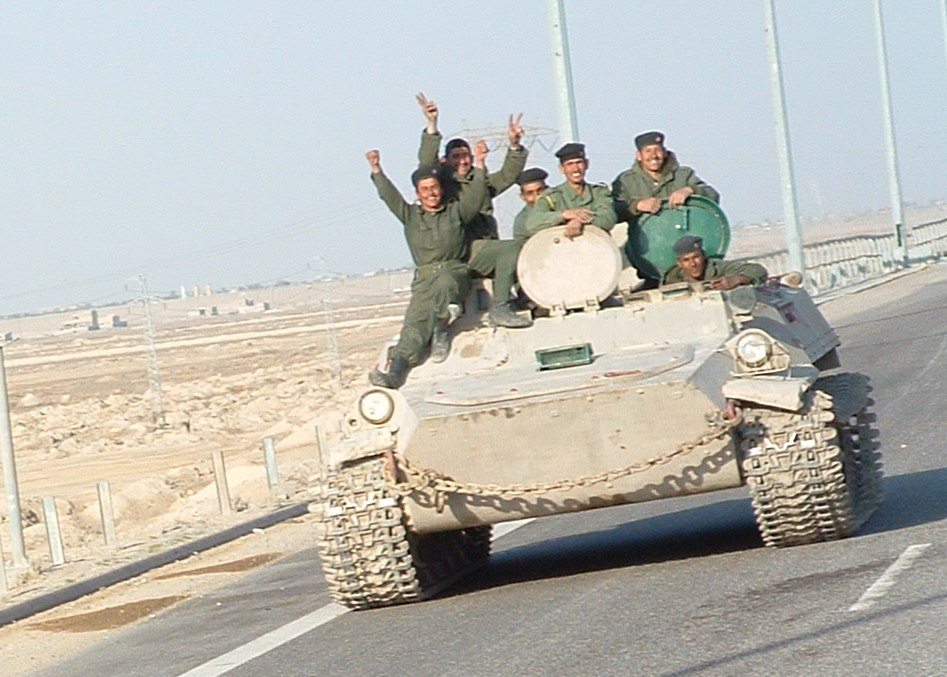 Iraqi military men riding on tank