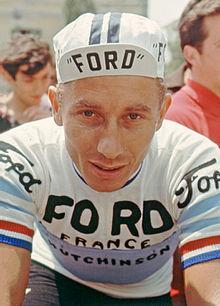 Photographie d'un cycliste se tenant de face sur sa bicyclette.
