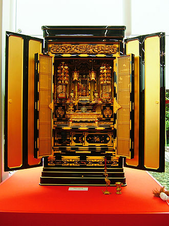 Butsudan - An ornate butsudan with open doors displaying an enshrined Amida Buddha. A Butsudan in the Jodo Shinshu Buddhism tradition.