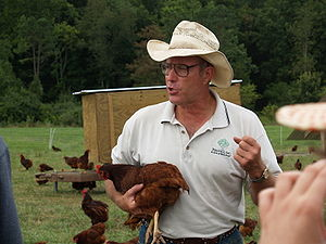 Joel Salatin holds a hen during a tour of Poly...