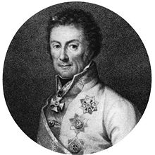Klenau has dark curly hair; he wears a white military coat, and military decorations.