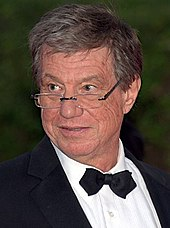 Director John McTiernan dressed in a tuxedo looks to his right