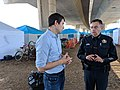 Josh Harder speaks with a police officer at a homeless encampment.jpg