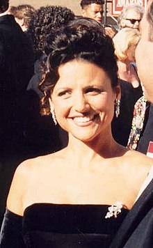 A woman with black hair tied in a knot wearing a black dress, at a crowded event.