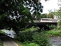 Kaiserbrücke mit Fahnenschmuck der Freiburger Partnerstädte über der Dreisam und Straßenbahn.jpg