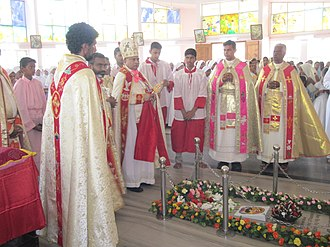 Christianity in India - Syro-Malabar Catholic bishop Mar Mathew Arackal (holding the Mar Thoma Cross which symbolises the heritage and identity of the Syrian Church of Saint Thomas Christians) along with other priests at the tomb of Servant of God March Varghese Payyappilly Palakkappilly
