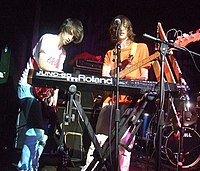 "An electric guitarist and a bassist are on stage beside a ""JUNO-60 Roland"" synthesiser keyboard, which is being played by the guitarist. A drum kit is in the background."