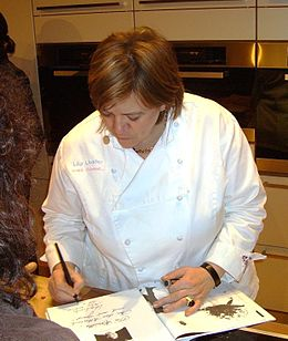 Lea Linster signs one of her cookbooks.JPG