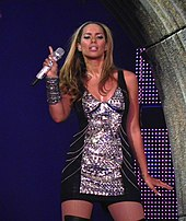 A picture of a woman wearing a short black and metallic dress, holding a microphone. She is facing forward.