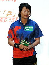 "An East Asian woman wearing a blue and red polo shirt and a ponytail. She holds in her right hand a microphone displaying a green rectangle with the words ""New Town Plaza"" in white; this composition is also present in her shirt."