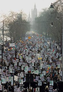 A large crowd, some of whom are carrying banners walks through London. The protest against the Iraq War, in London, February 2003, forms a backdrop to the events of Saturday.