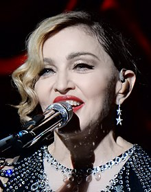 Madonna smiling with a microphone in front of her mouth