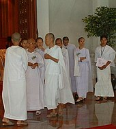 Nine Asian women dressed in white robes are standing and talking. Eight are shaven, one is not.