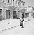 Man met baby in een deken gewikkeld al lopend door de straten van Mea Shearim, Bestanddeelnr 255-2472.jpg