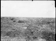 a black and white image of barren land. In the mid-ground is two field artillery guns, with teams of men at each gun, firing from left to right.