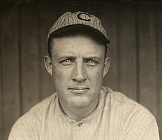 "A man in a striped white baseball jersey wearing a striped gray baseball cap with a ""C"" at the centre."