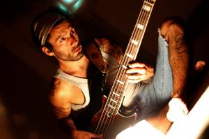 Outtaseezun musician on bass guitar.png