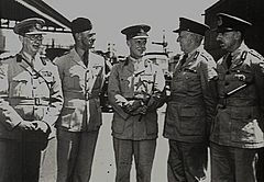 Five men in light-coloured military uniforms