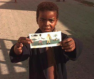Psychological Operations (United States) - A Somali boy holding up a leaflet dispersed during Operation Restore Hope in the early 1990s
