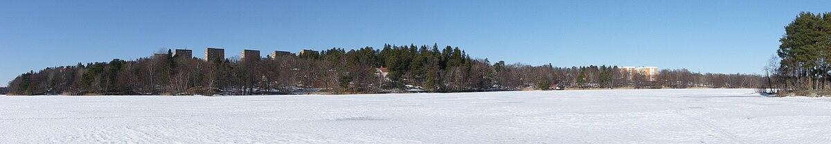 Vy over den østlige del af Farsta strand fra Magelungen is i marts 2011.   På bjerget ligger Svenske boligers lejekaserner i 10 etager tegnedes af Bertil Karlén, til højre derom blandt træerne, skimter Gyllings parcelhus og længst ud i højrekant ses en del af øen Kaninholmen.