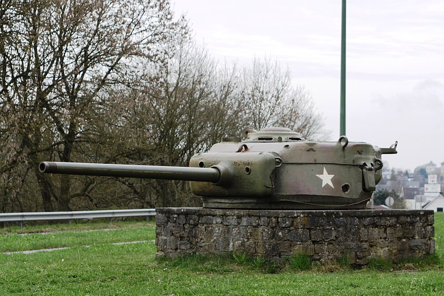 Turrets of Sherman Tanks defining the perimeter of the siege of Bastogne: N15 road to Neufchateau, N4 road to Marche, N34 road to Houffalize, N874 road to Longvilly, N84 road to Wiltz, N4 road to Martelange. This one is on the N874. The left flank of the turret is penetrated by an 75 mm or 88 mm hit.