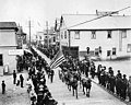 Parade with horse drawn carriage, soldiers and spectators on the sidewalk, Nome, Alaska, July 28, 1906 (AL+CA 2396).jpg