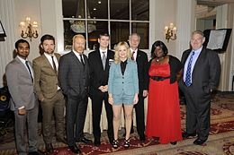 Six cast members and the series' creators dressed formally and posing at the awards hall