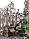 foto van Hoekhuis met rijk gebeeldhouwde halsgevel en drie gebeeldhouwde trapvensters in de zijgevel
