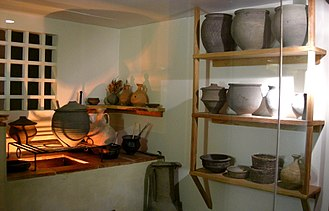 Olla (Roman pot) - Ollae of varying shapes in a reconstruction of a Roman kitchen; top shelf, and on the rack over the fire