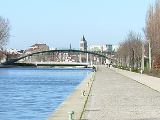 Saint-Denis, Seine-Saint-Denis - The Canal Saint-Denis with swing bridge, pedestrian overpass leading to the Stade de France and the Basilique Saint-Denis in the background.