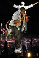 Sean Kingston wearing jeans and a grey shirt, singing on stage.