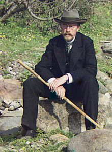 Prokudin-Gorsky seated on a rock holding a walking cane