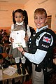 Sgt Angela Redford distributing T-shirts to school children (4290089774).jpg