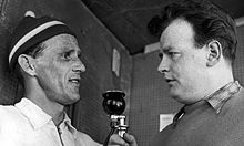 Sixten Jernberg, left, is being interviewed by another man, on the right, who is holding a microphone.