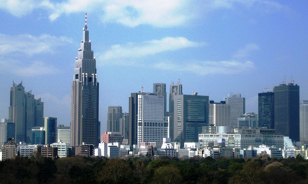 Mid-level view of a city; the tops of trees in the foreground with many high-rise buildings in the background