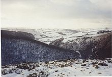 A thin covering of white snow with rocks poking through it, covering sloping hillsides.