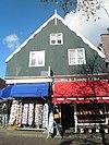 foto van Huis voorzien van een houten voorschot met uitgeschulpte windveren
