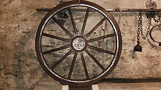 Breaking wheel - An execution wheel (German: Richtrad) exhibited in the Museum of Cultural History Franziskanerkloster in Zittau, Saxony, Germany, dated in the centre with year 1775. Bolted to the lower rim edge is an iron blade-like thrust attachment