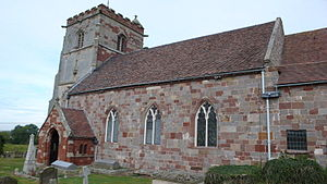 The nave of a stone church seen from the southwest, containing three pointed windows and a small porch, with a battlemented tower beyond