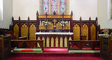 Panoramic photograph of the hand carved and painted cedar woodwork in the St John's chancel, with red carpet