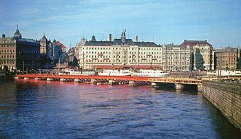 Strömbron under uppförande 1946 och sedd från samma plats år 2010. Bron grundlades provisorisk på träpålar, som sticker upp över vattenytan, vilket framgår på bilden från 1946. I bakgrunden syns Grand Hôtel innan takvåningen påfördes.