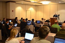 A man speaking from a podium to a room of people with laptop computers