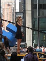 Une jeune femme aux cheveux blonds et bouclés lève les yeux tout en étant vêtue d'une robe de cocktail noire et debout sur un taxi.