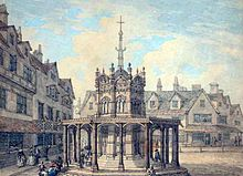 Squat octagonal structure, surrounded by tall thin buildings. A tall narrow structure, also octagonal, rises from it, topped by a cross.