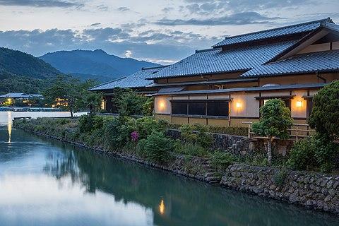 Togetsu Café old building with yellow lights at sunset on the river bank of Saganakanoshimacho island, Kyoto, Japan
