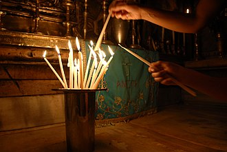 A pilgrim places candles in the tomb of the church Tomb of Jesus Jerusalem (2008-01).jpg